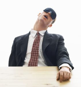 Businessman asleep at desk with eye mask on